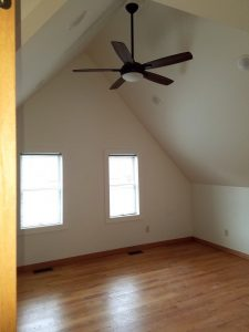 Eaved bedroom with ceiling fan and wood floor