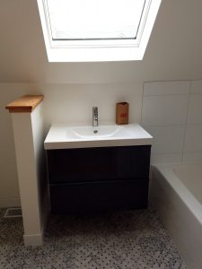 Modern bathroom sink next too tub, skylight overhead